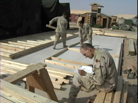 4th May 2005 MONTAGE US soldiers building new construction framework and conversing about what goes where / FOB Speicher Iraq / AUDIO