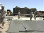 4th May 2005 MONTAGE US Soldiers shoveling concrete for new construction female soldier finishing concrete / FOB Speicher Iraq / AUDIO