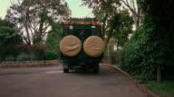 A 4x4 car drives away into a compound, Kenya.