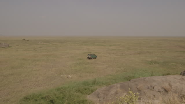 A 4x4 vehicle drives out onto the wide open plains of the Serengeti, Tanzania.