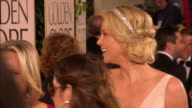 69th GOLDEN GLOBE AWARDS ARRIVALS HD MCU/CU Charlize Theron walking along crowded red carpet smiling greeting and talking w/unidentified people at...