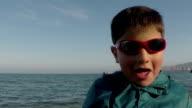 a boy in sunglasses on the beach