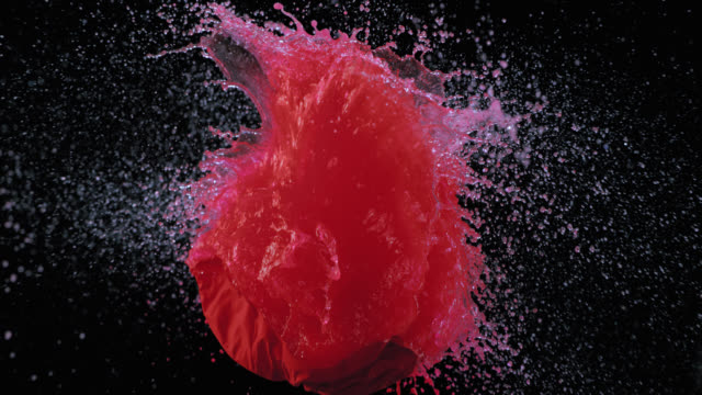 SLO MO of a bullet piercing a red water balloon