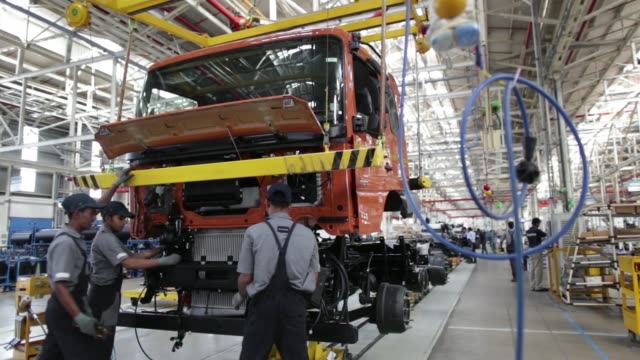 WS a hoist crane transports the cabin of a BharatBenz truck on a cart on the production line