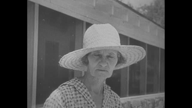 MS a large white house / gables windows and clapboards of house / Mrs Houston leaves front door of house wearing a sunhat / CU Houston removing hat...