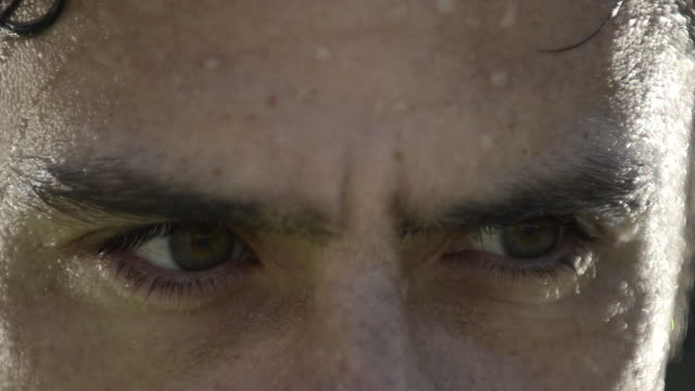 ECU of a male tennis player's eyes and intense expression, sweaty.