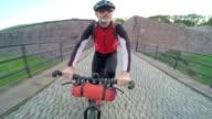 POV of a man biking through a park outside of a Euopean City.