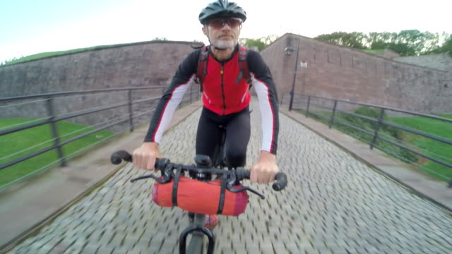 POV of a man biking through a park outside of a Euopean City.