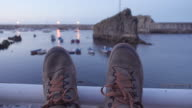 4K | POV of a man resting at a sea fishing port at dusk. Mountain boots on the foreground and fishing boats defocus on the background.