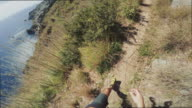 POV of a Man trail running on a single track on high cliff