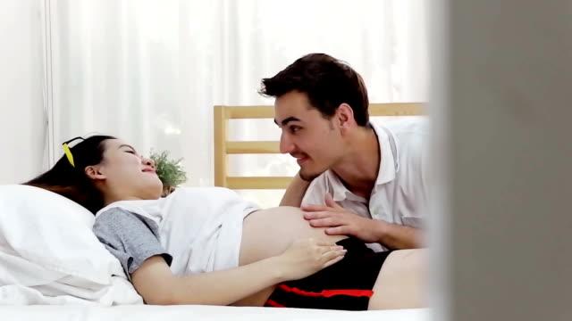 iemands hand zachtjes aanraken van zijn vrouw zwangere buik, terwijl ze samen in bed liggen