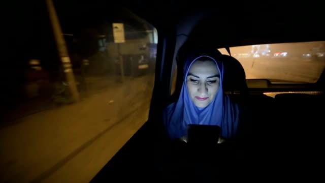 eine moderne arabische Frau fährt in einem Auto in der Nacht