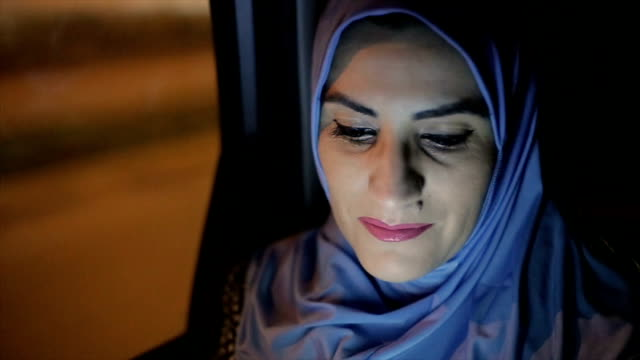 a modern Arab woman rides in a taxi at night