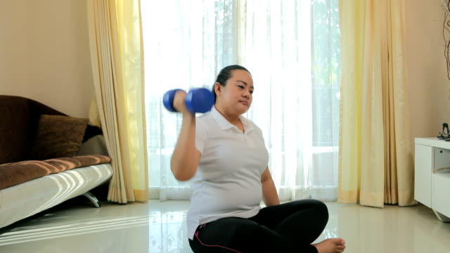 Fat woman does fitness with dumbbell