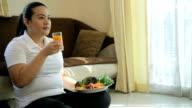 Grasso donna bere succo d'arancia