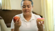 Fat woman selects a doughnut or apple