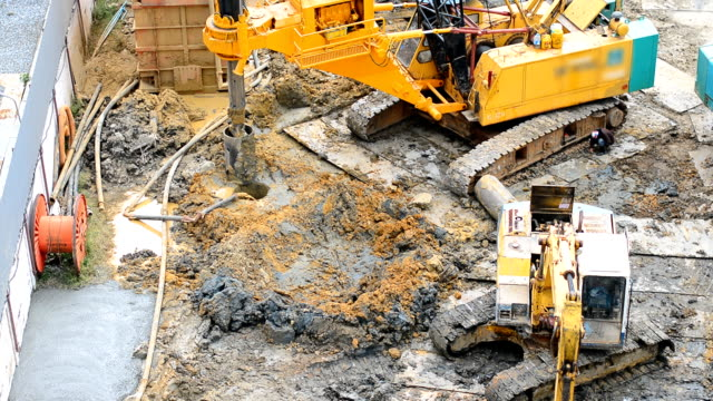 a yellow crane truck is working  for digging