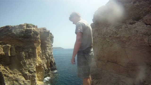POV of a young man jumping off a cliff and doing a backflip in Malta. - Model Released - HD