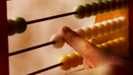 Abacus or counting frame, hands of person using the calculating tool