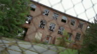 MS, CANTED, Abandoned factory building seen through chain link fence, Beacon, New York, USA