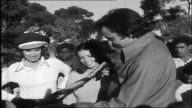 aboriginal man gives Johnny Cash a carved aboriginal walking stick and chats with Johnny as June Carter Cash stands beside Johnny while he looks at...