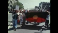 Aboriginal people demonstration street march chanting for land rights Holding an Aboriginal flag / close up man with loud hailer / Placard sign 'We...