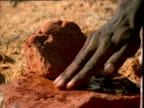 Aborigine makes rock paint in outback, Northern Territory, Australia
