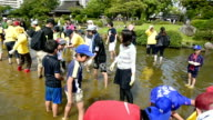 About 500 volunteers gathered in Kumamoto's Chuo Ward on May 21 Japan to help clean up the pond in the wellknown Suizenji Jojuen traditional Japanese...