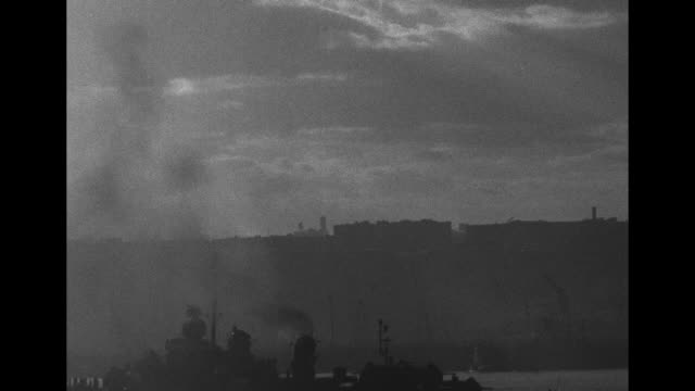 About 60 bombers fly in formation overhead / battleship USS Missouri moves across foreground at dusk / VS USS Missouri fires salute at dusk clouds /...