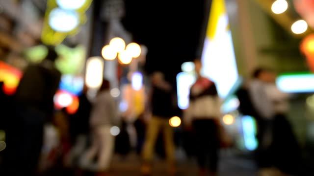 Abstract blurred background of Pedestrians walking on street and Night illumination of Namba Zone in Osaka, Japan