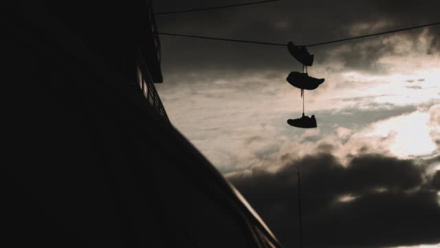 Abstract cinematic shot of sneakers hanging on a power line in Brooklyn at sunset.