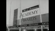 Academy Awards 36th Annual arrivals 1 Santa Monica Civic Auditorium outside sign 'Academy Awards' Sandra Dee Bobby Darin Army Archerd interviewer...