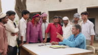 Accountant explaining to labours, Haryana, India
