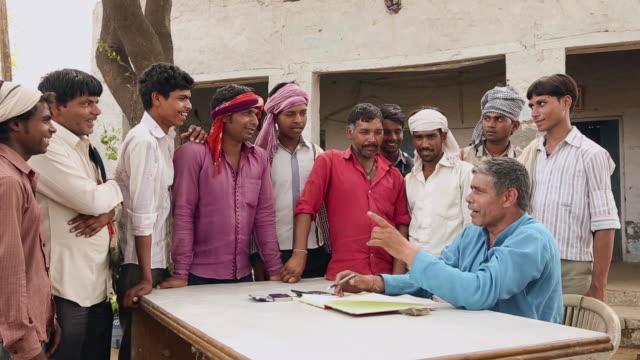 Accountant explaining to labours, Haryana, India