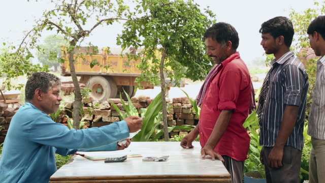 Accountant giving wages to labours, Haryana, India