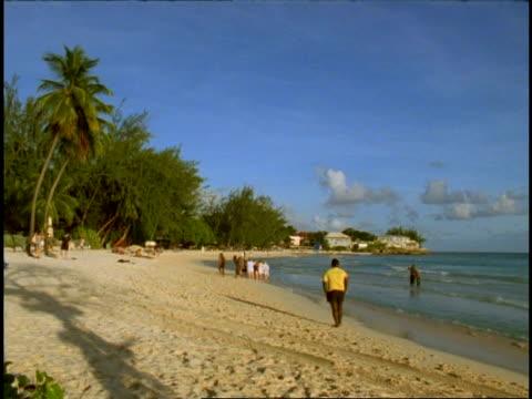 Accra Beach, Barbados - WA people strolling along beautiful tropical sandy beach, palm trees, buildings on horizon