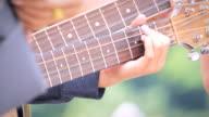 Akoestische gitarist spelen van akkoorden, close-up.