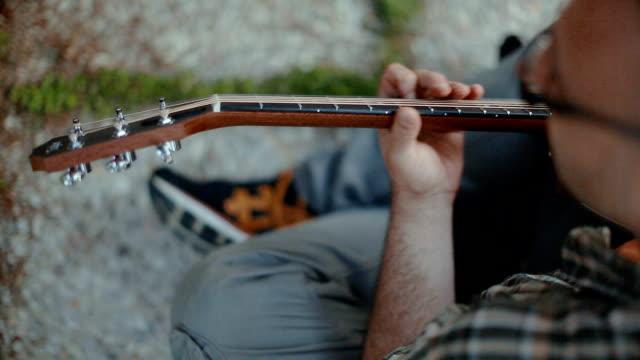 Akoestische gitarist spelen van akkoorden, hoge hoekmening