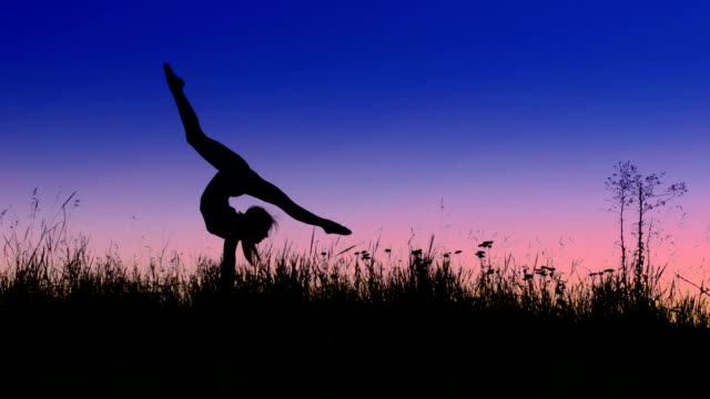 Acrobat girl exercising in the evening field arrow position