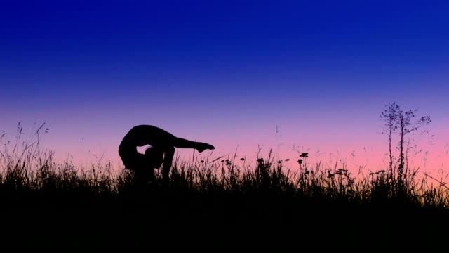 Acrobat girl exercising in the evening field. Scorpio position