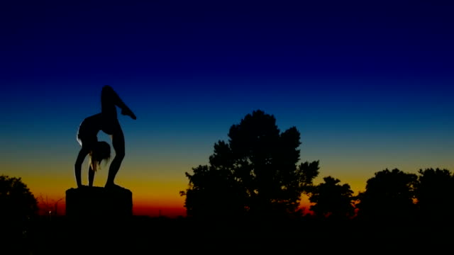 Acrobat girl exercising on column in the evening  Arrow position