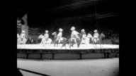Acrobats come into the ring jumping on a giant trampoline / a child heavy audience watches acrobat on stilts / performers on horseback / a bear on...