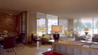 PAN across 1950s mid-century modern living room with original furnishings, bridge table, sofa, side tables, lamps and a dining area with wet bar
