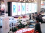 RIGHT across a section of the AMC display at the 1959 Chicago Auto Show Ramblers and Ambassadors are visible throughout the display / WS ground level...