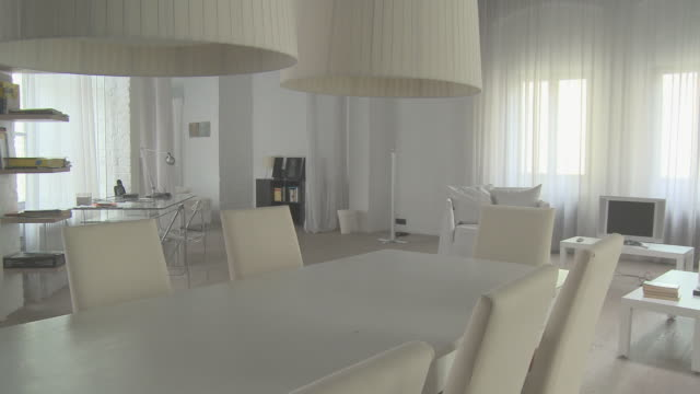 MS PAN across dining table to living room area in loft decorated entirely in white/ Berlin, Germany