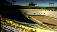 Across empty stadium field scoreboard over suites press boxes BG shadow of lights on grass field blue sky Old City Stadium Packers football NFL sports