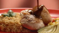 CU PAN across Mexican chicken mole dish served with rice and pico de gallo salsa as mole sauce is poured over chicken breasts