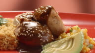 CU PAN across Mexican chicken mole dish served with rice as sesame seeds are sprinkled over the mole sauce