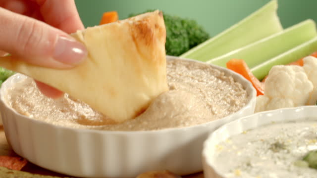 CU PAN across party platter as pita bread dips into hummus and celery stick dips into tzatziki appetizer