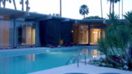 WS TS across swimming pool and garden side of mid-century modern country club home at dusk